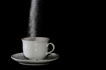 trickles: sugar trickles into a white cup