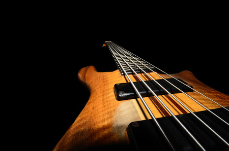 bass guitar strings with wooden close up black background