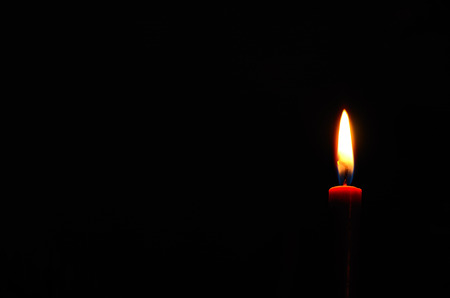 doctor burnout: red glowing and burning candle in the dark
