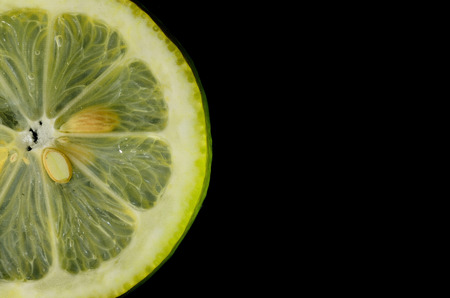 citrus family: fresh yellow lemon wedge and black background