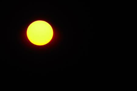 brightly shining sun and black sky
