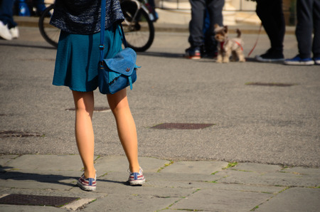 miniskirt: woman in a short miniskirt and sneakers in the city