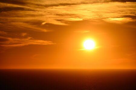 orange sunset: warm bright orange sunset by the sea Stock Photo