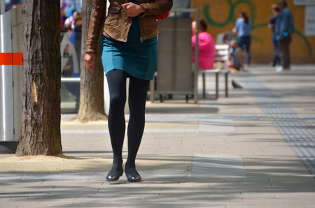 miniskirt: woman in blue miniskirt and dark pantyhose in the city Stock Photo