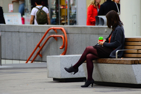 commercially: young woman with red pantyhose sits in the city Stock Photo