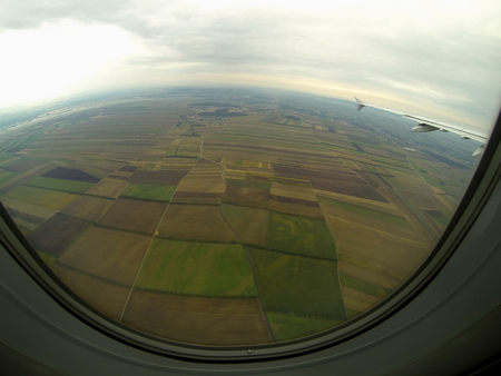 green brown: view of airplane on many green brown fields