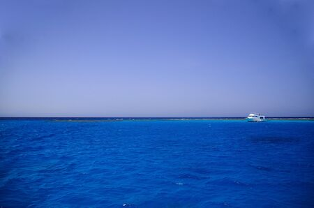 seawater: blue clear seawater and white ship at coral reef Stock Photo