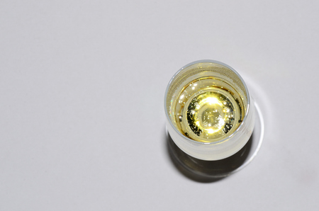 glass with bubbly champagne from above with white background