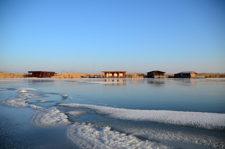 on the skids: colorful shacks on frozen lake in winter Stock Photo