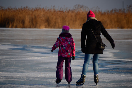 on the skids: Mother and daughter ice skating on the lake