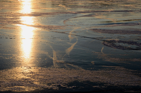 on the skids: skating traces on lake in winter with warm sun