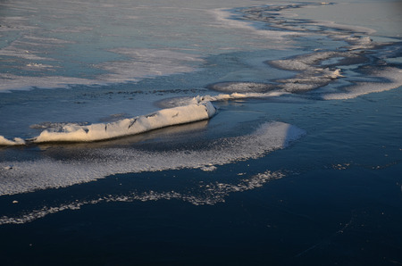 on the skids: long crack in the ice with snow on the lake