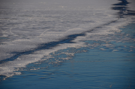 on the skids: long crack in the ice on the lake in the winter