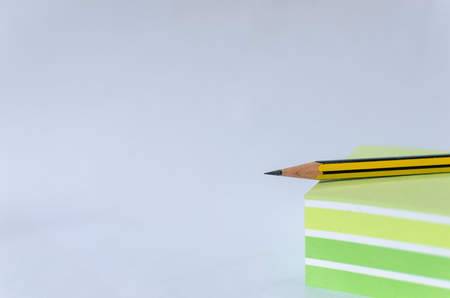 writing materials: block with pencil and white background Stock Photo
