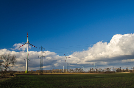 wind force: many pinwheels and electricity pylons on fields Stock Photo