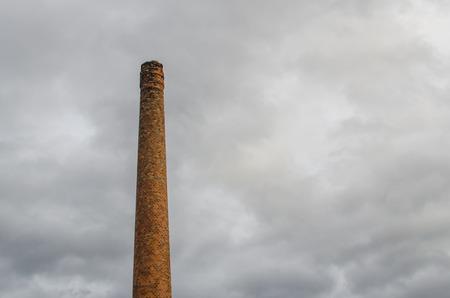 production facility: old chimney and gray sky Stock Photo