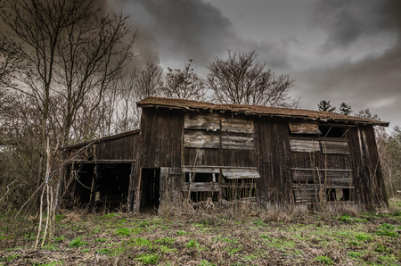 abandoned old wood barn with rain clouds