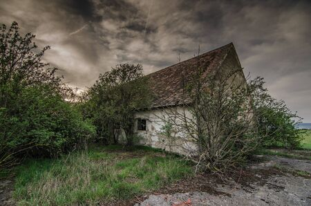 uninhabited: old house with dark rain clouds