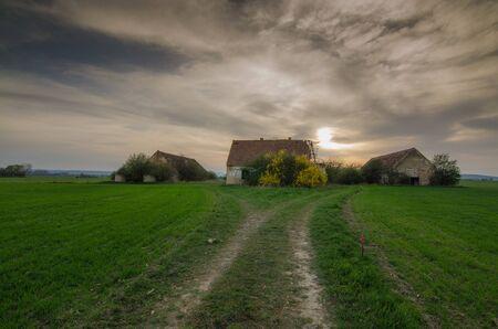 uninhabited: abandoned old farm with sunset Stock Photo