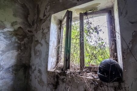 going places: overgrown window with helmet in abandoned house Stock Photo