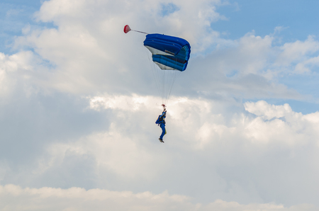 blue parachute jumpers in the sky with clouds Stock Photo