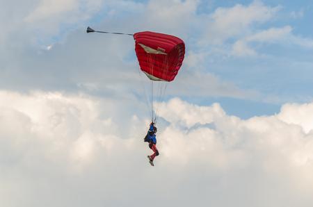 caida libre: Paracaídas rojos en el cielo Foto de archivo