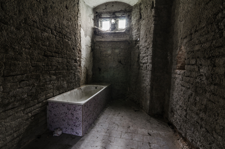 going places: room with old bricks and purple bathtub Stock Photo