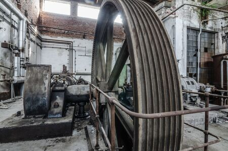 paper factory: large drive wheel in abandoned paper factory