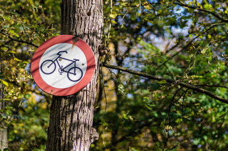 sign with pointing prohibition of bicycle on tree in forest Stock Photo
