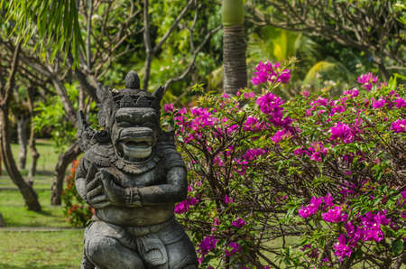 statue and many pink flowers at a temple