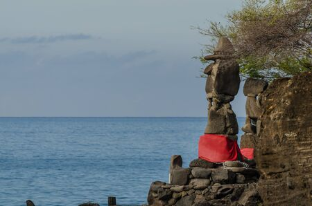 high statue with hat at temple and sea in Bali Stock Photo