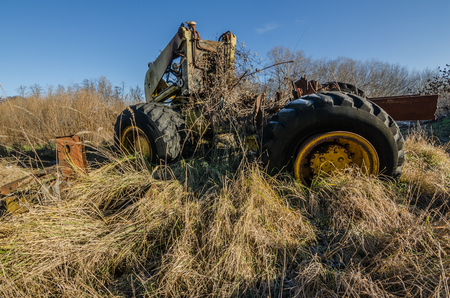 old overgrown dredge in high grass