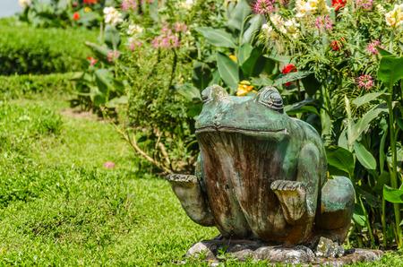 green frog figur in garden complex