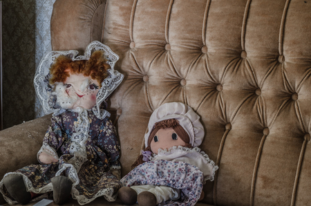 two dolls on brown sofa in abandoned house