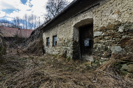 overgrown farmhouse made of stone in the mountains Stock Photo