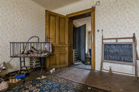 Room with blackboard and cot in an abandoned house