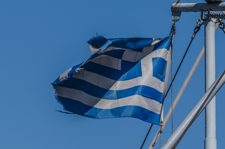 torn Greek flag on a ship by the sea Stock Photo