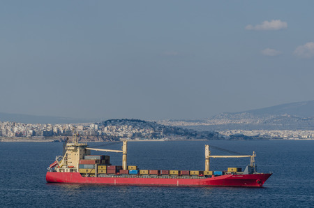container ship and city athens by the sea