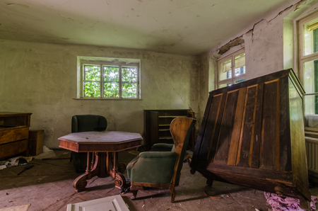 table with armchair and box in an old house Stock Photo
