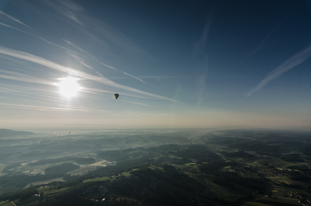 landscape with hot air balloon and bright sun Stock Photo