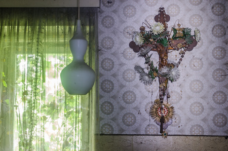 Old cross on a wall with wallpaper Editorial