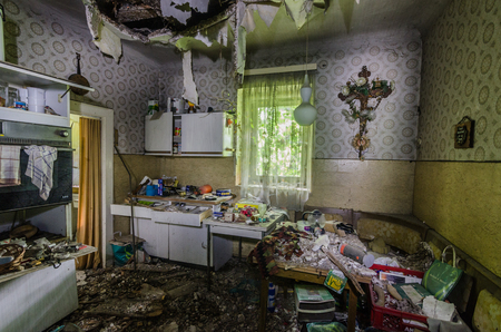 dilapidated kitchen with cross and many objects