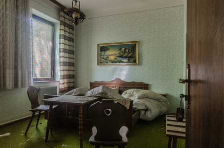 room with bed and table in an abandoned hotel