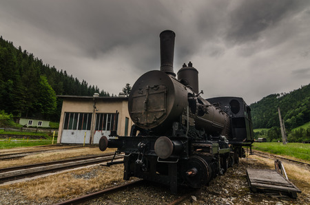Old steam locomotive with rain clouds in the mountains