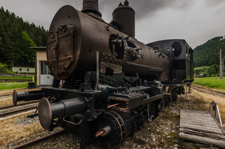 Old steam locomotive on a train station in the mountains