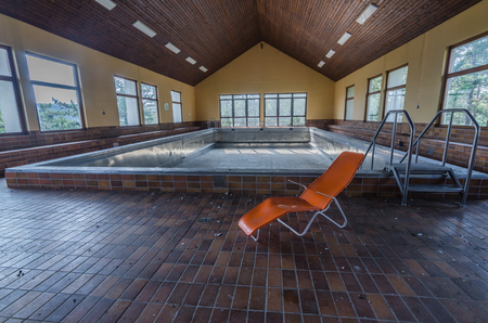 Orange lounger in a deserted empty swimming pool
