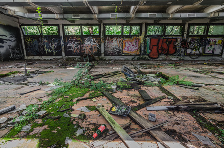 Old abandoned factory building with graffiti and moss