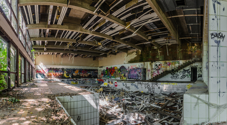 many colorful graffiti in ruined indoor swimming pool panorama view