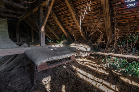 bed in abandoned attic of a house
