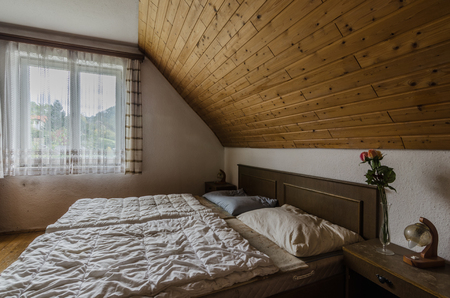 empty room with bed in attic of old inn